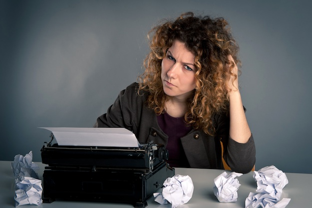 Young desperate girl writing with an old typewriter. Conceptual image.